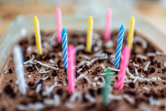 Closeup macro view of homemade chocolate raw vegan coconut cake with cacao nibs beans with colorful pink blue ad yellow birthday candles