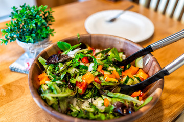 Closeup of fresh green salad in bowl plate with mixed lettuce, bell peppers with potted plant in rustic wooden table Fototapete