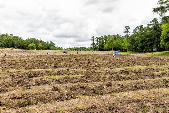 Crater of Diamonds Park with brown soil in Arkansas dirt landscape meadow field and people digging searching for minerals