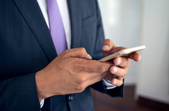 Close up of hispanic business man texting with a smart phone iphone 6 in formal suit at the office.