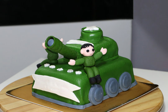 Green army tank cake with edible soldier doll.