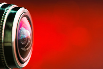 Camera lens with red backlight. Side view of the lens of camera on red background. Red  camera Lens close Up. Gorizontal photo