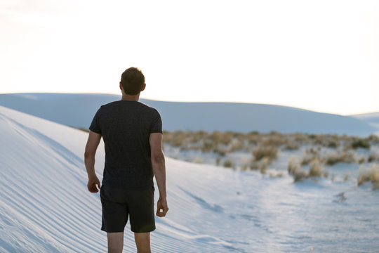 Man back walking on sand in white sands dunes national monument in New Mexico looking at sunset
