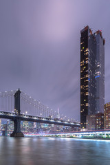 Financial District with Manhattan Bridge and One Manhattan Square building from East River at night with long exposure
