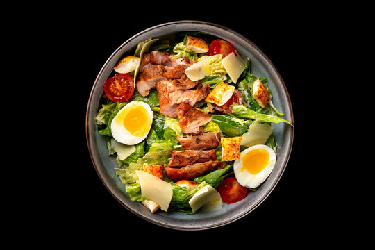 Top view image of caesar salad isolated at black background.
