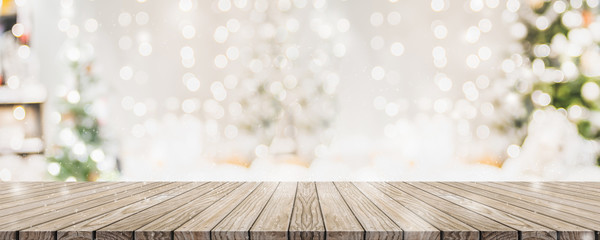 Empty woooden table top with abstract warm living room decor with christmas tree string light blur...