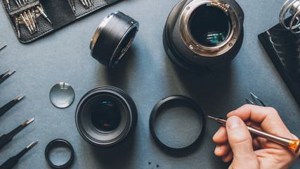 Digital device tech support. Top view of man hands repairing photo camera optical dslr lens.
