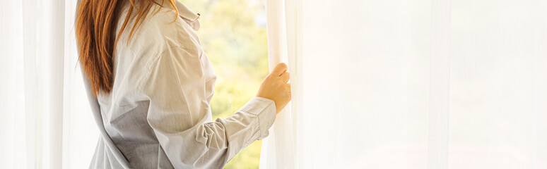 Young beauty woman wake up and stand in front of window in the morning, Cropped image