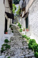 Obraz Narrow street with stairs between the old stone houses at district of Mangalem in Berat, Albania. The albanian ancient city of Berat, designated a UNESCO World Heritage Site in 2008.  - fototapety do salonu