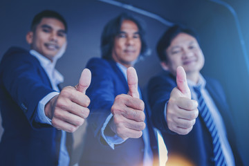 Successful professional team businessman in suit showing thumbs up sign.