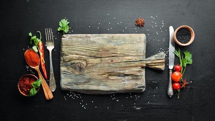 Fototapete - The background of cooking. On a black wooden background. Top view. Free space for your text.