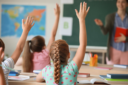 Cute little pupils raising hands during lesson in classroom
