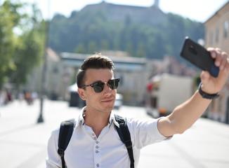 Student / tourist taking self portrait in the European city