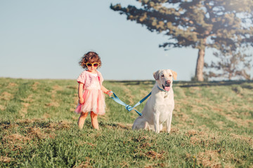 Portrait of cute stylish little Caucasian child girl in sunglasses walking dog in park field outside on summer sunny day at sunset. Kid playing with domestic animal pet. Happy childhood concept.