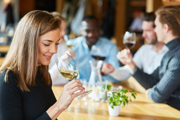 Woman is drinking a glass of wine on a wine tasting