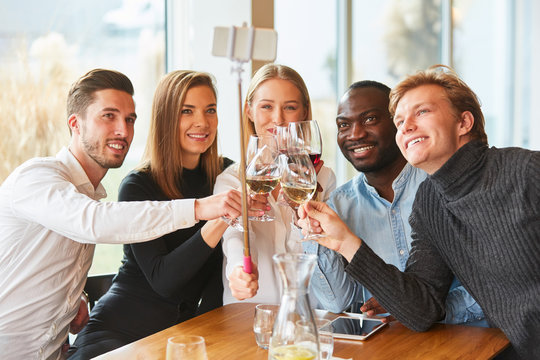 Young people in the restaurant toast with wine