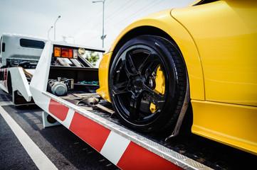 Flat bed tow truck loading a broken vehicle. Roadside service