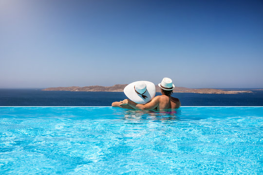 Traveler couple with sunhats hugging in a infinity pool and enjoying the view to the mediterranean sea