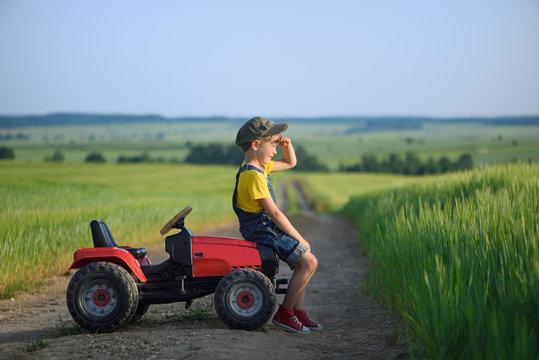 Little boy farmer on a tractor among green grain fields