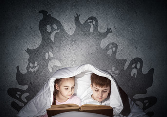 Engrossed little kids reading book in bed