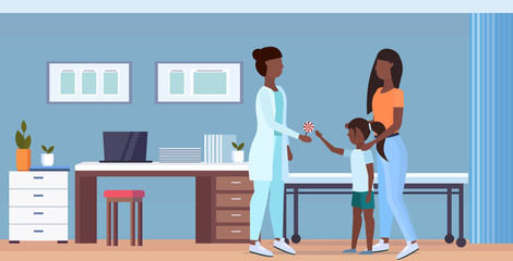 mother with daughter visiting african american doctor pediatrician giving lollipop to little girl consultation healthcare concept modern hospital interior full length flat horizontal