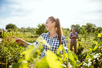 Young and happy farmer's couple at their garden in sunny day. Man and woman engaged in the cultivation of eco friendly products. Concept of farming, agriculture, healthy lifestyle, family occupation.