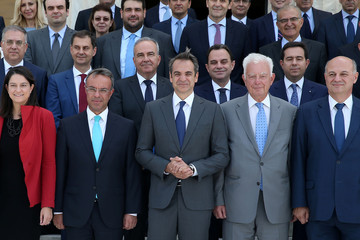 Greek Prime Minister Kyriakos Mitsotakis and members of the new government pose for a group picture after the first meeting of the new cabinet at the parliament building in Athens