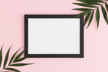 Top view of a black frame mockup with palm leaf decoration on a pink background. Landscape orientation.