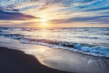 Sea at sunset. Sun reflection in waves.