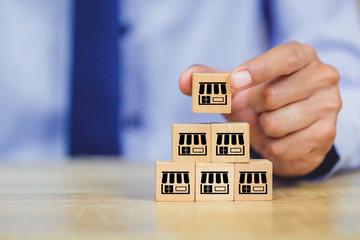 Franchise business concept , businessman hand choose wood blog with franchise marketing.