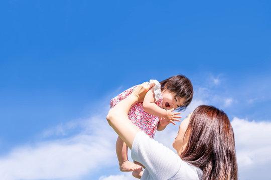 青空の下、赤ちゃんを高い高いをしてあやすお母さん。家族、母子、親子、幸せ、愛、育児、子育てイメージ