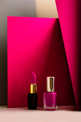 set of lipstick and nail polish, on modern colored background