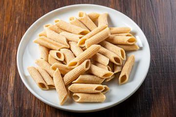 Fototapete - pasta, wholemeal penne on white plate