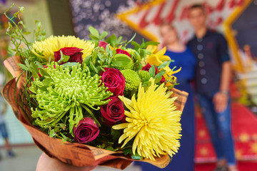 A bouquet of beautiful flowers, a couple of young people in the background out of focus
