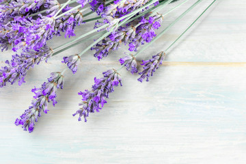 A fresh bouquet of blooming lavender flowers, shot from the top on a rustic wooden background with a place for text