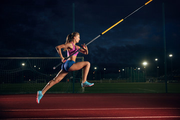 Fototapeta Ready to overcome difficulties. Professional female pole vaulter training at the stadium in the evening. Practicing outdoors. Concept of sport, activity, healthy lifestyle, action, movement, motion. obraz