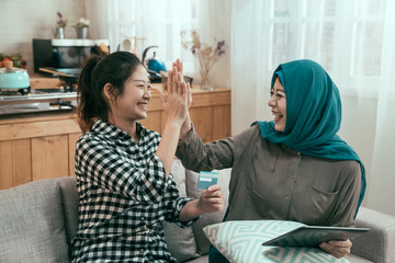 vintage style picture of group asian young female people happy giving high five with palms celebrating successful shopping on online summer sale. two arabic and japanese ladies friends using tablet.