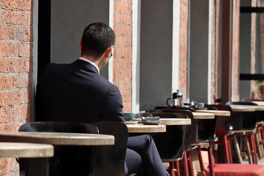 Stylish man in a business suit sitting at a table in street cafe. Concept of lunch alone, waiting for a date or business meeting, coffee break