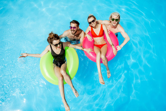 Group of a happy friends having fun, swimming with inflatable toys in the swimming pool outdoors, view from above