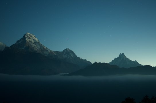 Wide shot of beautiful rocky mountains with amazing clear blue sky with stars in the background