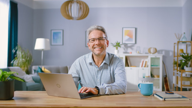 Handsome Middle Aged Man Uses Laptop Computer and Smiles on Camera. He is in the Cozy and Stylish Living Room. Happy Successful Man Works on Computer from Home.