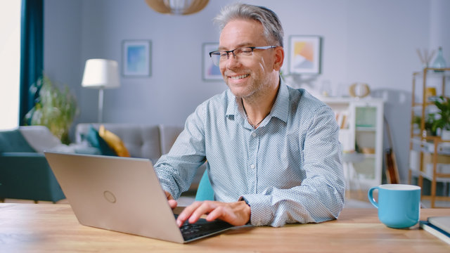 Handsome Middle Aged Man Uses Laptop Computer While Sitting at His Desk in the Cozy and Stylish Living Room. Happy Successful Man Works on Computer from Home.