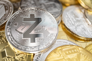 Zcash zec physical coin on the stack of other different cryptocurrencies. Close-up photo of zcash with shallow depth of field