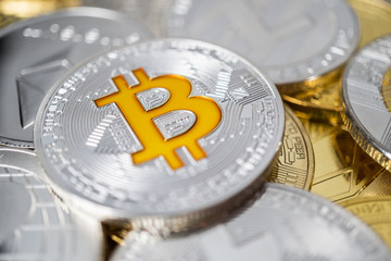 Bitcoin physical coin on the stack of other different cryptocurrencies. Close-up photo of bitcoin with shallow depth of field
