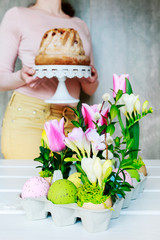 Easter floral decoration with colorful eggs, tulips, freesias and buxus
