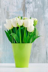 Bouquet of white tulips in green vase.