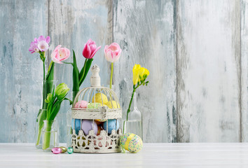 Basket with Easter eggs and flowers in glass bottles