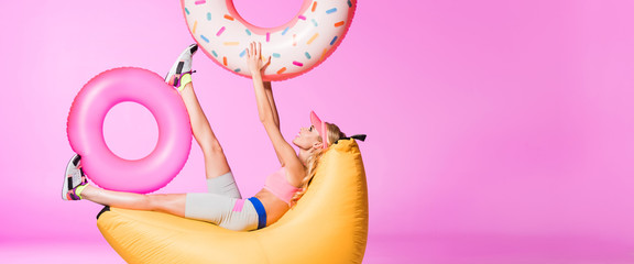 panoramic shot of girl on bean bag chair with inflatable swim rings on pink, doll concept