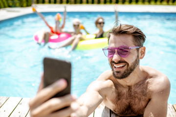 Handsome man takng selfie photo with phone, while resting in the swimming pool with friends...