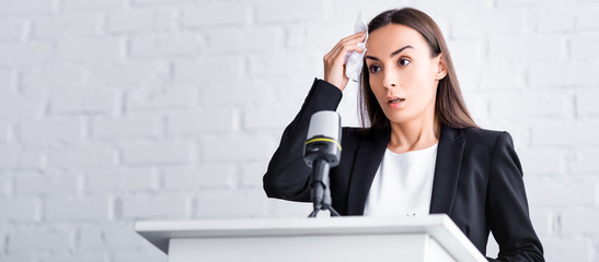 panoramic shot of worried lecturer suffering from fear of public speaking holding napkin near forehead while standing on podium tribune Wall mural